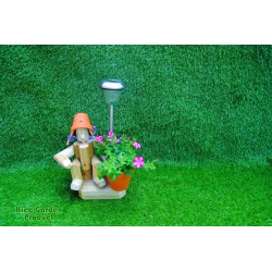 Sitting girl holding a pot with solar light